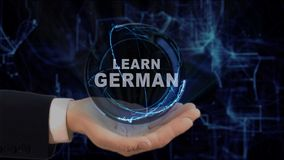 Painted hand shows concept hologram Learn German on his hand. Drawn man in business suit with future technology screen and modern cosmic background Royalty Free Stock Photography