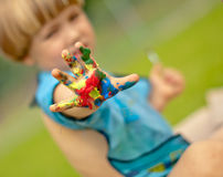 Painted hand of a small boy. A small boy shows his colourfully painted hand painted hand Royalty Free Stock Images