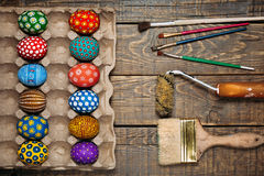 Painted in handmade Easter eggs and paint brushes on a wooden background Royalty Free Stock Photos