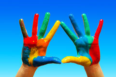Painted hands, colorful fun. blue sky. Painted hands, colorful fun. Creative, funny and artistic means happy! Blue sky background Stock Images