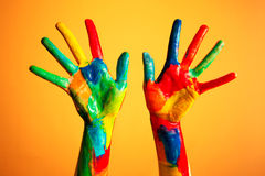 Painted hands, colorful fun. Orange background. Painted hands, colorful fun. Creative, funny and artistic means happy! Orange background wall Stock Photo