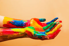 Painted hands, colorful fun. Orange background Stock Images