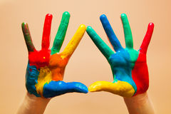 Painted hands, colorful fun. Orange background Stock Photo
