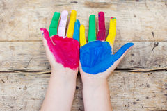 Painted hands. Colorful painted hands over the wooden background Royalty Free Stock Photo
