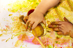 Painted hands smudging colors on messy table Stock Image