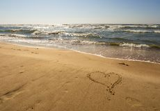 Painted heart on the golden sand of the Baltic beach in Palanga, Lithuania royalty free stock photo