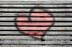 Painted heart. Red heart painted on a wooden bench stock images