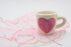 Painted heart-shaped cups placed on the fabric Royalty Free Stock Photo
