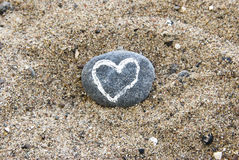 Painted heart on stone lying in sand Stock Photography