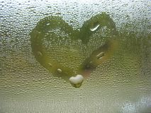 Painted heart on window glass and rain drops Stock Photography