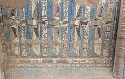 Painted hieroglyphic carvings on an ancient egyptian temple wall stock images