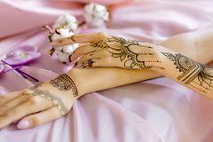 Painted Indian hand with mehndi ornament. Closeup slender female wrists painted with traditional indian oriental mehndi ornaments. Womens hands decorated with stock image