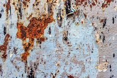 Painted iron background with a large rusty spot and metal corrosion. Painted metallic background with a large rusty spot and metal corrosion. Background royalty free stock image