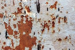 Painted iron surface with a large rusty spot and metal corrosion. Painted iron surface with a large rusty, black spot and metal corrosion. Old background with royalty free stock image