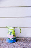 Painted jug. An antique jug painted with pink roses standing against a grey wall royalty free stock photography