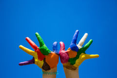 Painted kids hands on blue sky backgrobnd royalty free stock photography