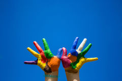 Painted kids hands on blue sky backgrobnd royalty free stock photos