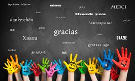 Painted kids hands in front of a blackboard with the message `thank you` in many languages