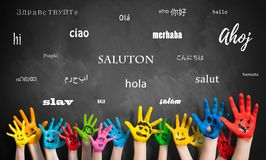 Painted kids hands in front of a blackboard with the word `hello ` in many languages stock photo