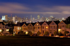 Painted Ladies at Alamo Square. Night lays down her garments on the iconic Painted Ladies and downtown San Francisco Stock Photos
