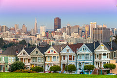 The Painted Ladies of San Francisco, California sit glowing amid Royalty Free Stock Images