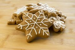Painted light brown ginger breads, white icing, Christmas cookies, shapes - snowflakes, tree. Star, bamboo table Royalty Free Stock Photos