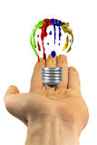 Painted light bulb hover above hand Royalty Free Stock Images