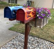 Painted Mail boxes. Artistic Painted mail boxes red and blue with flames and flower pot stock images
