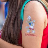 Painted mascot of the World Cup soccer Wolf zabiyaka on the hand of the girl. Russia, Samara, July 2018: painted mascot of the World Cup soccer Wolf zabiyaka on royalty free stock photo