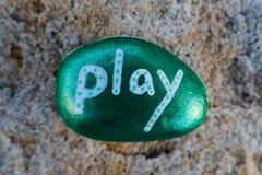 Painted metallic green rock that states Play Royalty Free Stock Image