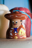 Painted Mexican bell doll. A small ceramic bell painted to look like a man in traditional Mexican clothing, with candles in the background Royalty Free Stock Photos