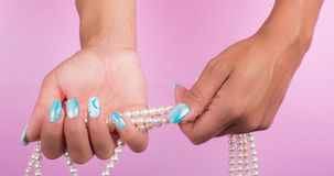 Painted nails and pearls Royalty Free Stock Image