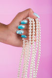 Painted nails and pearls Stock Photos