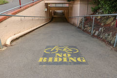 Painted No Bike Riding sign on a pedestrian subway Stock Images