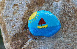 Painted ocean and sailboat scene on a rock. Amateurish painted scene on a small rock which is on a bigger rock.  Scene is blue sky and ocean, yellow and red Royalty Free Stock Photos