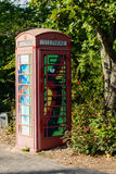 Painted old red phone booth, phone box, painted in different col Stock Image