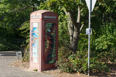 Painted old red phone booth, phone box, painted in different col Royalty Free Stock Photography