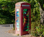 Painted old red phone booth, phone box, painted in different col Royalty Free Stock Photos