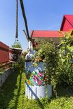 Painted old well and bucket decorated with a hand painted colorful floral motives, folk art, Zalipie, Poland. ZALIPIE, POLAND - AUGUST 2, 2018: Painted old well stock photo