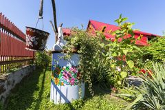 Painted old well and bucket decorated with a hand painted colorful floral motives, folk art, Zalipie, Poland. ZALIPIE, POLAND - AUGUST 2, 2018: Painted old well stock photos