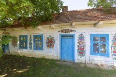 Painted old wooden cottage decorated with a hand painted colorfu flowers, Zalipie, Poland. ZALIPIE, POLAND - AUGUST 3, 2018: Painted old wooden cottage decorated royalty free stock images