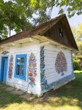Painted old wooden cottage decorated with a hand painted colorful flowers, Zalipie, Poland. ZALIPIE, POLAND - AUGUST 2, 2018: Painted old wooden cottage royalty free stock photo