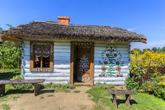 Painted old wooden cottage decorated with a hand painted colorful flowers, Zalipie, Poland. ZALIPIE, POLAND - AUGUST 3, 2018: Painted old wooden cottage royalty free stock photo