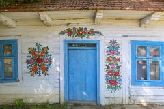 Painted old wooden cottage decorated with a hand painted colorful flowers, Zalipie, Poland. ZALIPIE, POLAND - AUGUST 3, 2018: Painted old wooden cottage stock images