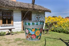 Painted old wooden cottage, well and pail, decorated with a handmade painted flowers, Zalipie, Poland. ZALIPIE, POLAND - AUGUST 3, 2018: Painted old wooden stock photo