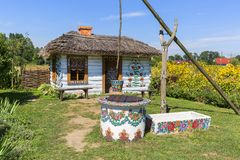 Painted old wooden cottage, well and pail, decorated with a handmade painted flowers, Zalipie, Poland. ZALIPIE, POLAND - AUGUST 3, 2018: Painted old wooden royalty free stock photo