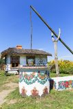 Painted old wooden cottage, well and pail,folk art, Zalipie, Poland. ZALIPIE, POLAND - AUGUST 3, 2018: Painted old wooden cottage, well and pail, decorated with stock photography