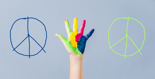 Painted peace sign in girl's hand against war. Royalty Free Stock Image