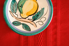 Painted Plate on Red Table Cloth Royalty Free Stock Image
