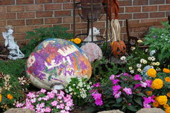 Painted pumpkin. Decoration surrounded by flowers Stock Photography